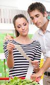 Couple Checking A Long Supermarket Receipt