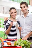 foto of receipt  - Smiling couple at store holding a long grocery receipt with shopping cart on foreground - JPG