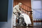 Nurse Helping Elderly Woman In Wheelchair At Home