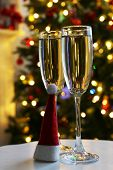 Two champagne glasses with red Santa hat on table, on fir-tree background