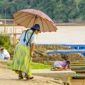 RURRENABAQUE, BOLIVIA, MAY 10, 2014 - Local woman with umbrella on riverbank of Beni river