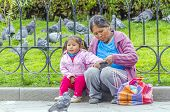 LA PAZ, BOLIVIA, MAY 9, 2014:  Local woman with a little daughter plays with a pigeon at Plaza Murillo