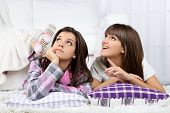 Beautiful girls twins in pajamas with pillows at home