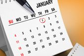 Composite image of january on calendar against orange vignette