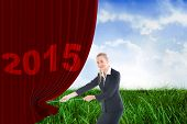 Businesswoman pulling a rope against field of grass under blue sky