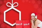 Festive blonde lying with sale shopping bags against blurred christmas background