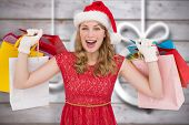 Excited blonde in santa hat holding shopping bags against blurred christmas decorations on wood