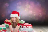 Woman in santa hat laying on the floor while holding gifts against shimmering light design over boards