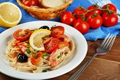Tasty pasta with shrimps, mussels, black olives and tomato sauce on plate on wooden background
