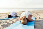 fitness, sport, people and lifestyle concept - close up of couple making yoga exercises on mats outdoors