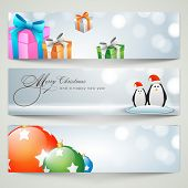 Merry Christmas celebration banner or website header design with gifts, Xmas Balls and penguin couple in Santa hat.