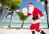 christmas, holidays and people concept - man in costume of santa claus running with clock showing twelve over tropical beach background