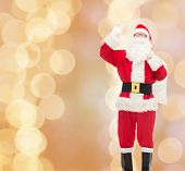christmas, holidays, gesture and people concept - man in costume of santa claus with bag waving hand over beige lights background