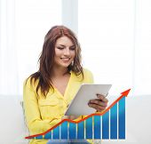people, technology, statistic sand business concept - smiling woman with tablet pc computer and growth chart at home