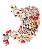 Colored pills, tablets and capsules on a white background in the form of a stomach