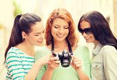 tourism, travel, leisure, holidays and friendship concept - smiling teenage girls with camera outdoors