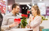 Постер, плакат: love romance valentines day couple and people concept happy young man with red flowers giving p