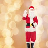 christmas, holidays, gesture and people concept - man in costume of santa claus pointing finger up over beige lights background