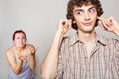 stock photo of yell  - An angry woman yelling at her husband happy man closed his ears with his hands - JPG