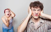 pic of yell  - Angry woman yelling at her husband the unfortunate man closed his ears with his hands - JPG
