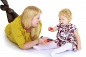 pic of montessori school  - Mom and daughter lying on the floor and playing educational games - JPG