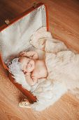 Newborn baby lying in a brown suitcase.