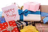 Pile of colorful gifts with greeting card on white background