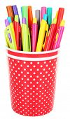 Colorful pens and markers in red polka-dot plastic cup isolated on white background