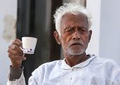 Older Man With White Hair Drinks Coffee.