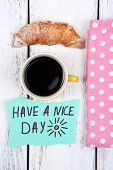 Composition of coffee, fresh croissant and paper card on napkin, on wooden background