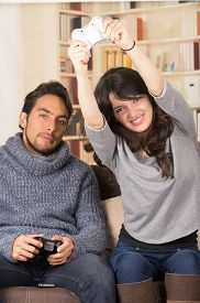 picture of grils  - young cute gril winning while playing video games with boyfirend in livingroom - JPG