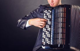 pic of accordion  - Musician playing the accordion against a black background - JPG