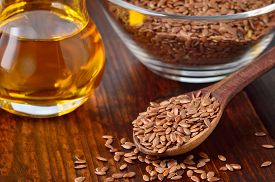 picture of flax seed oil  - Brown flax seeds on spoon and flaxseed oil in glass jug on wooden table. Flax oil is rich in omega-3 fatty acid.