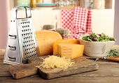 foto of grating  - Grated cheese on wooden table on cutting board in kitchen - JPG