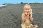 picture of tropical food  - After playing on the sea black sand beach little cute girl picnics of natural vegetarian food  - JPG