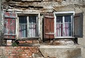 pic of abandoned house  - Two weathered windows with shutters and curtains in the ruin of an abandoned house - JPG