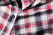 foto of button down shirt  - Close up detail of a red plaid button up style shirt - JPG