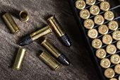 image of top-gun  - Scattering of small caliber cartridges on a wooden background - JPG