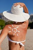 pic of sun tan lotion  - Tanning lotion in the shape of sun on woman - JPG
