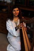 stock photo of celtic  - Young woman playing celtic harp in a white angelic historical costume