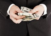 picture of one hundred dollar bill  - Businessman counting one hundred dollar bills close up - JPG