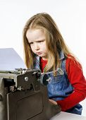 stock photo of typing  - Cute little girl typing letter on vintage typewriter keyboard - JPG