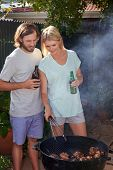 stock photo of tong  - Women helping boyfriend husband at outdoor garden barbecue with tongs and beer - JPG