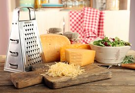 picture of grating  - Grated cheese on wooden table on cutting board in kitchen - JPG