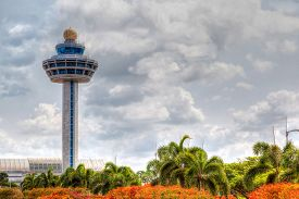 foto of controller  - HDR rendering of Singapore Changi International Airport Traffic Controller Tower with cloudy skies in the background and beautiful trees and shrubs in the foreground - JPG