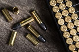 stock photo of cartridge  - Scattering of small caliber cartridges on a wooden background - JPG