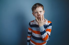 stock photo of finger-licking  - teenager boy of about ten European appearance Brown put his finger in his mouth on a gray background - JPG