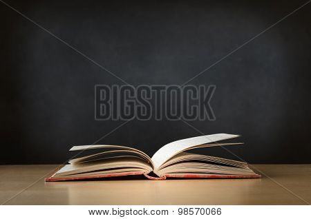 Old Book Opened On Desk With Chalkboard In Background
