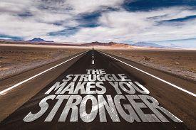 stock photo of struggle  - The Struggle Makes You Stronger written on desert road - JPG