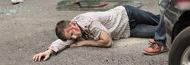 picture of street-walker  - Seriously injured man is lying on street - JPG